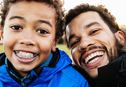Father and son smiling in park